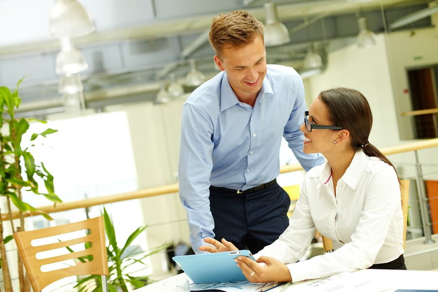 Happy businessman consulting with secretary by workplace at meet